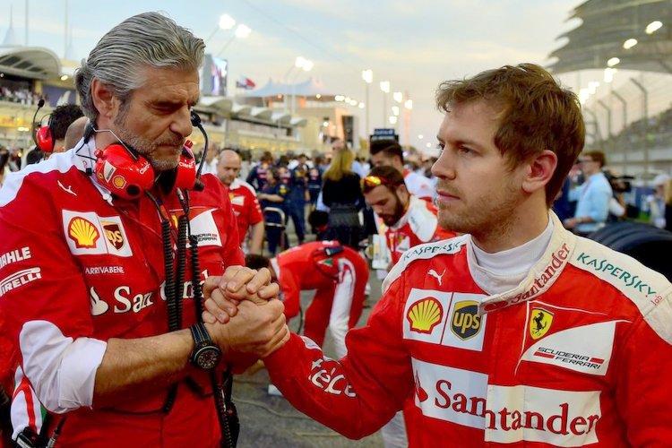 Ferrari's German driver Sebastian Vettel (R) shakes hands with team principal of the Scuderia Ferrari Formula One team Maurizio Arrivabene (C) in the pit lane ahead of the Bahrain Formula One Grand Prix at the Sakhir circuit in Manama on April 3, 2016. AFP PHOTO / ANDREJ ISAKOVIC