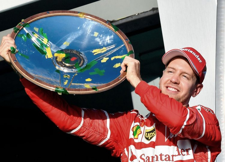 Ferrari's German driver Sebastian Vettel celebrates with the winner's trophy on the podium following his victory in the Australian Grand Prix in Melbourne on March 26, 2017. / AFP PHOTO / SAEED KHAN / --IMAGE RESTRICTED TO EDITORIAL USE - STRICTLY NO COMMERCIAL USE-- (Photo credit should read SAEED KHAN/AFP/Getty Images)