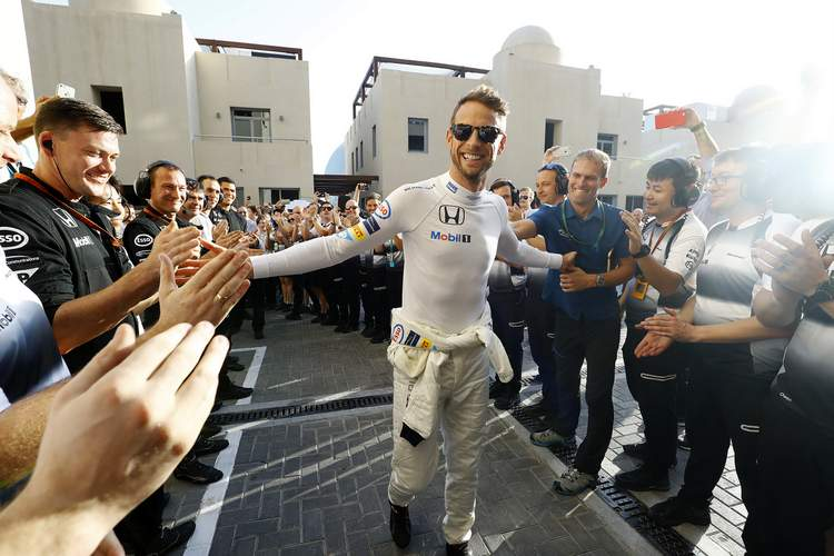 Jenson Button walks to the garage to the cheers of his team.