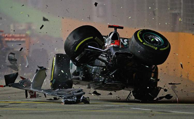 SINGAPORE - SEPTEMBER 23: Michael Schumacher of Germany and Mercedes GP crashes with Jean-Eric Vergne of France and Scuderia Toro Rosso during the Formula One Grand Prix of Singapore at Marina Bay Street Circuit on September 23, 2012 in Singapore. (Photo by Vladimir Rys/Getty Images)