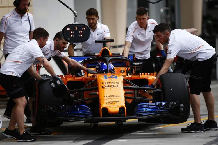 Bahrain International Circuit, Sakhir, Bahrain. Friday 6 April 2018. Mechanics push the Fernando Alonso McLaren MCL33 Renault in the pit lane. Photo: Andy Hone/McLaren ref: Digital Image _ONZ1554
