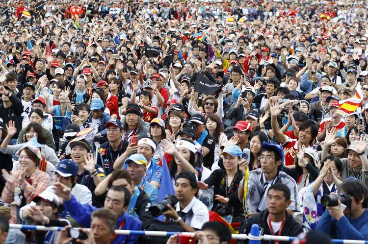 Fans watch Fernando Alonso on stage during a promotional event.