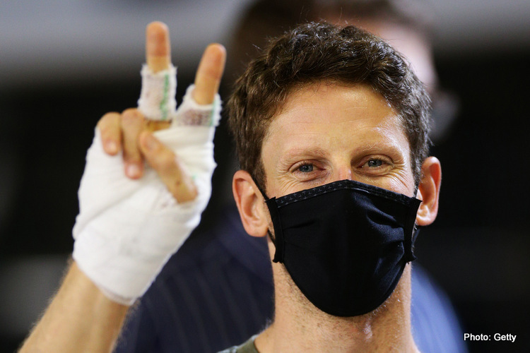 Romain Grosjean of France and Haas F1 puts up two of his bandaged fingers in the Pitlane during previews ahead of the F1 Grand Prix of Sakhir at Bahrain International Circuit on December 03, 2020 in Bahrain, Bahrain.