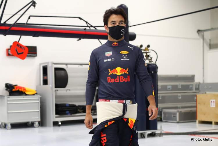 Sergio Perez of Mexico and Red Bull Racing walks in the engineering bays at Red Bull Racing