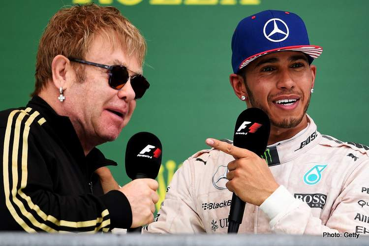 Lewis Hamilton of Great Britain and Mercedes GP celebrates on the podium with Elton John after winning